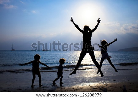 Mother and three kids silhouettes jumping on beach at sunset