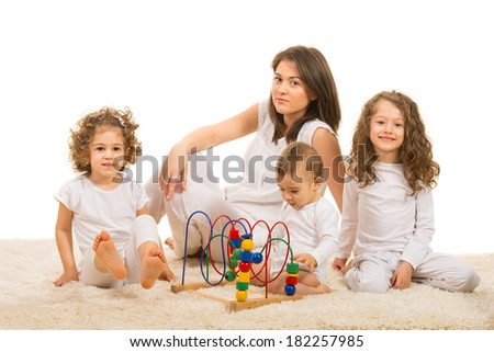 Mother and three kids sitting on carpet in their home - stock photo
