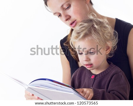 mother and three years old daughter reading a book - stock photo