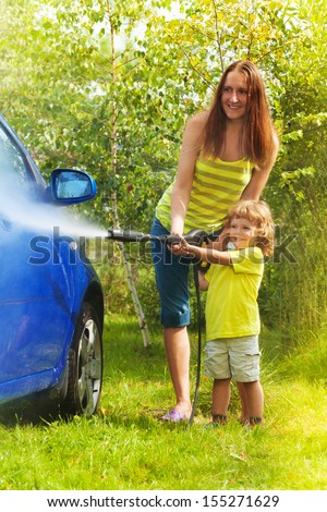 Mother and three years old son washing car with high pressure washer with boy pointing water nozzle  - stock photo