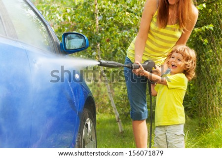 Mother and three years old son washing car with high pressure washer with boy pointing water nozzle  standing in outside in the yeard parking - stock photo