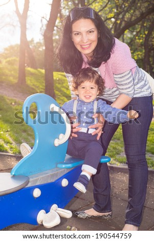 Mother and toddler boy having  fun in park on seesw and standing in sunbeam - stock photo