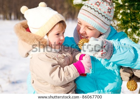 Mother and toddler daughter playing with Christmas decoration - stock photo