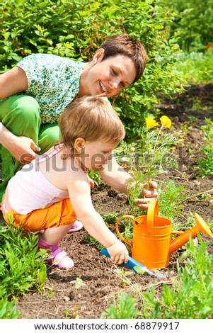 Mother and toddler daughter's spring gardening - stock photo