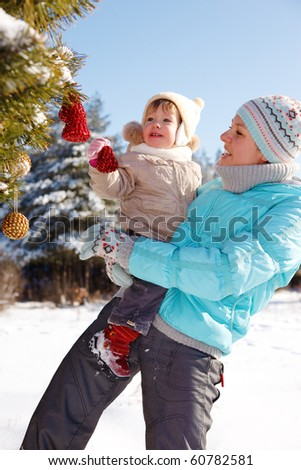 Mother and toddler girl decorating Christmas tree - stock photo