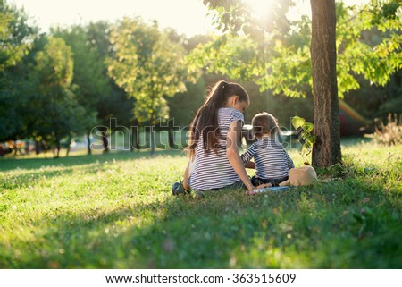 Mother and toddler sitting under the tree during summer leisure - stock photo