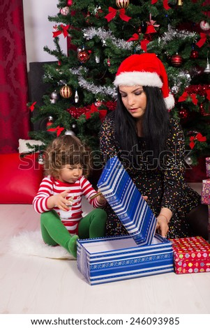 Mother and toddler son opening Christmas gifts under tree - stock photo