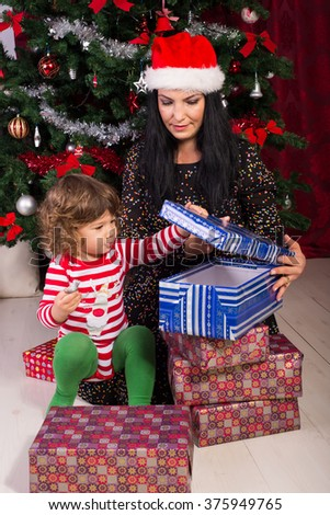 Mother and toddler son opening Christmas presents in their home