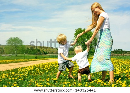 Mother and two children, a baby and a small child  holding hands and dancing and playing outside in a field of Flowers. - stock photo
