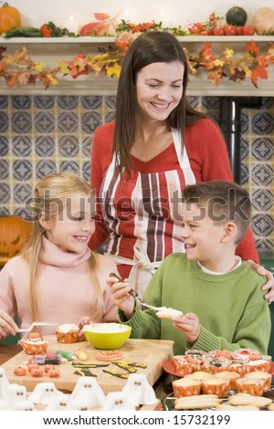 Mother and two children at Halloween playing with treats and smiling - stock photo
