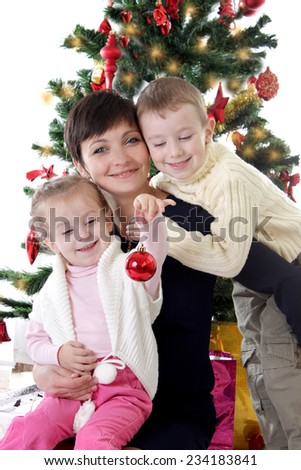 Mother and two children decorating Christmas tree over white