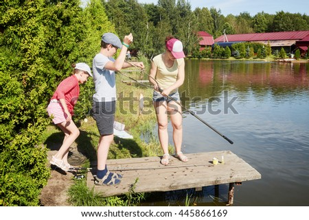 Mother and two children fishing at pond on sunny day.