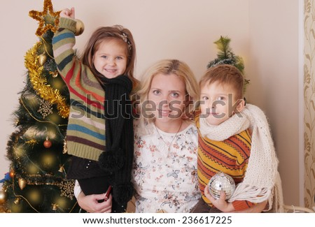 Mother and two children having fun over Christmas tree - stock photo