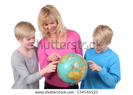 Mother and two children plan their next travel on the globe - stock photo