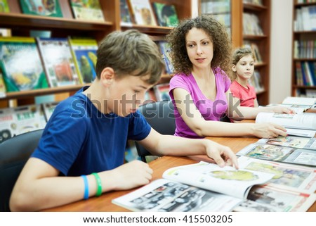 Mother and two children sit and read books in reading room of children library, focus on mother.  - stock photo
