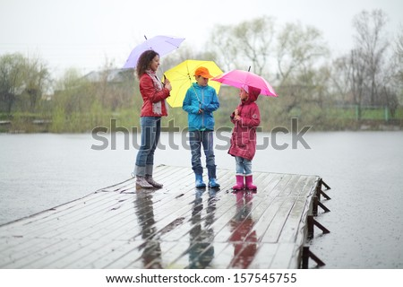 Mother and two children standing in the rain on a wooden pier - stock photo