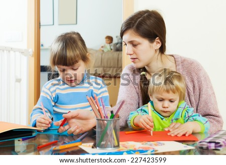 Mother and two children together with pencils in home