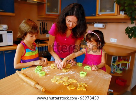 Mother and two daughters baking together in kitchen - stock photo