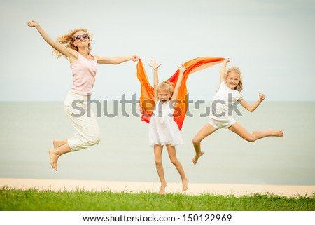mother and two daughters jumping at the beach - stock photo