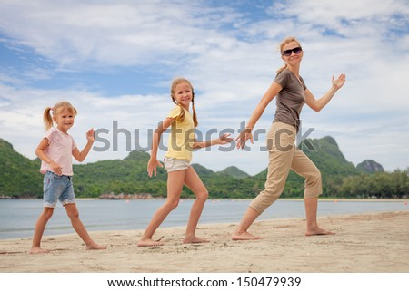 mother and two daughters playing on the beach - stock photo