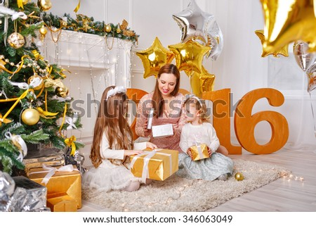 Mother and two daughters unpack gifts for New Year 2016. Family celebration. Holiday and fun. Merry Christmas. - stock photo