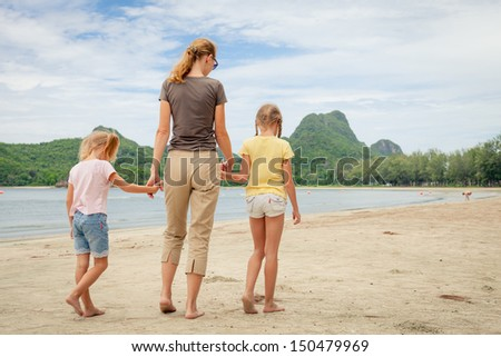 mother and two daughters walking on the beach