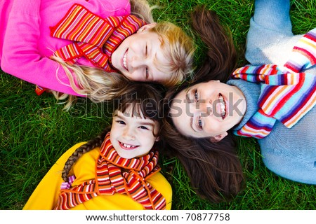 Mother and two girls in bright scarves lying on the grass