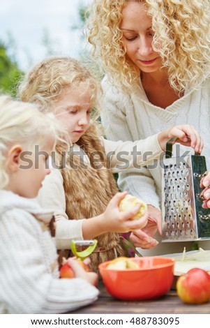 Mother and two girls rub apples together for a cake