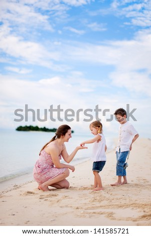 Mother and two kids at beach on cloudy day