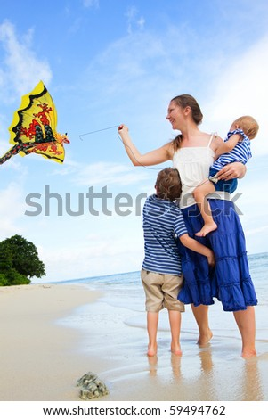 Mother and two kids flying kite on tropical beach - stock photo