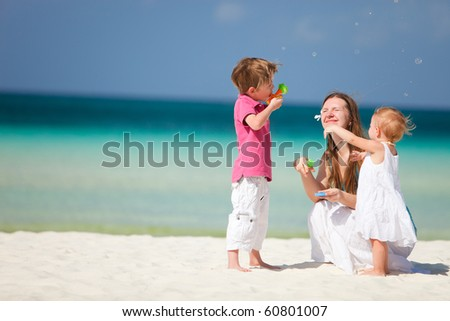 Mother and two kids having fun on beach making soap bubbles