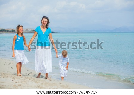 Mother and two kids having fun on tropical beach