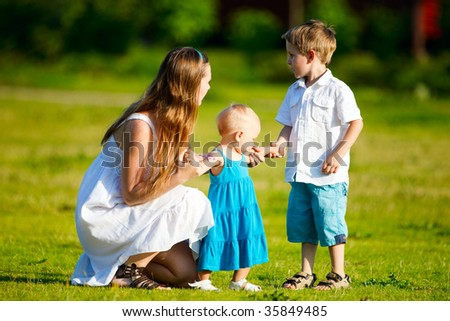 Mother and two kids having fun outdoors at sunny summer day