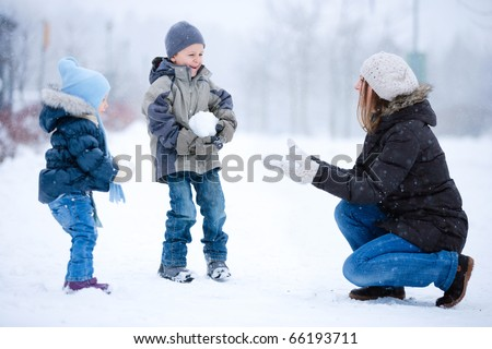 Mother and two kids having fun outdoors on beautiful winter day - stock photo