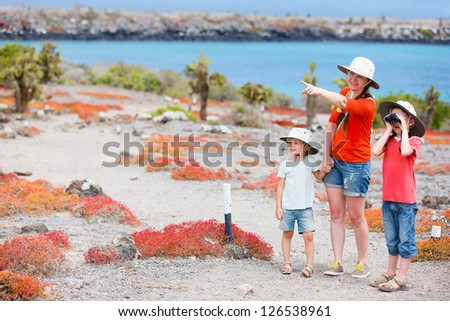 Mother and two kids hiking at scenic terrain - stock photo