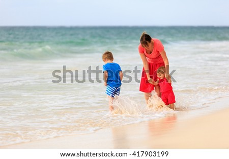 mother and two kids play at beach - stock photo