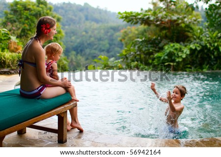 Mother and two kids playing in swimming pool