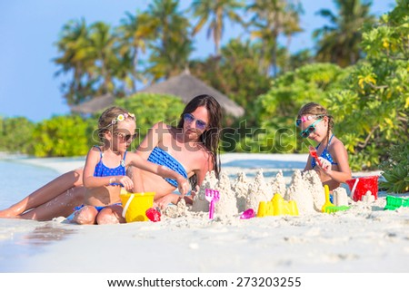 Mother and two kids playing with sand on tropical beach - stock photo