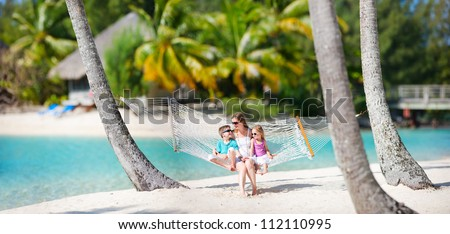 Mother and two kids relaxing on hammock at tropical beach - stock photo