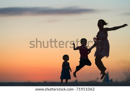 Mother and two kids silhouettes jumping on beach at sunset