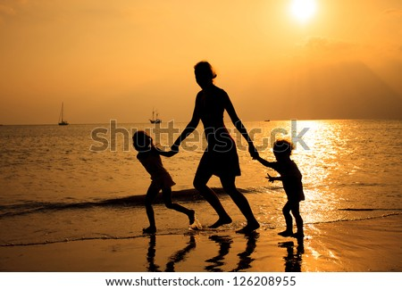 Mother and two kids silhouettes running on beach at sunset - stock photo