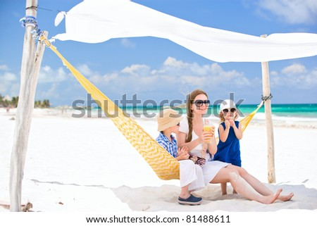 Mother and two kids sitting on hammock at tropical beach
