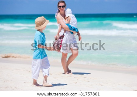 Mother and two kids walking along tropical beach - stock photo