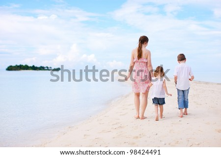 Mother and two kids walking at beach towards small island - stock photo