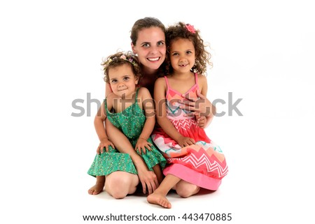 Mother and two mulatto daughter from interracial marriage or adoption. Children are sitting in her mothers lap looking at the camera. Isolated on white background. - stock photo