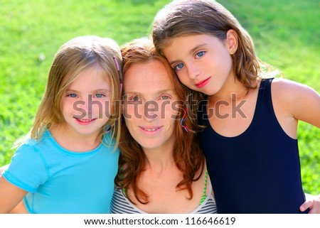 mother and two sister daughters in the garden park grass - stock photo