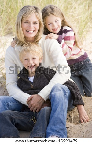 Mother and two young children sitting on beach smiling - stock photo