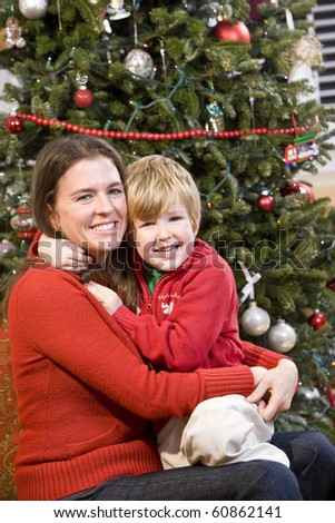Mother and 4 year old boy hugging in front of Christmas tree