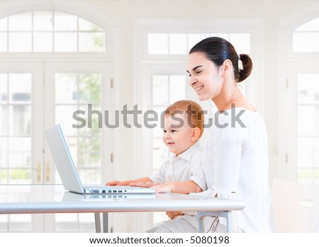 Mother and 2 years old baby boy sitting at the desk and using laptop computer. Indoor, brightly lit. - stock photo