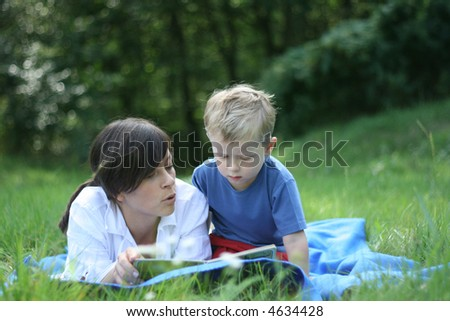 mother and 3-4 years old son reading book outside